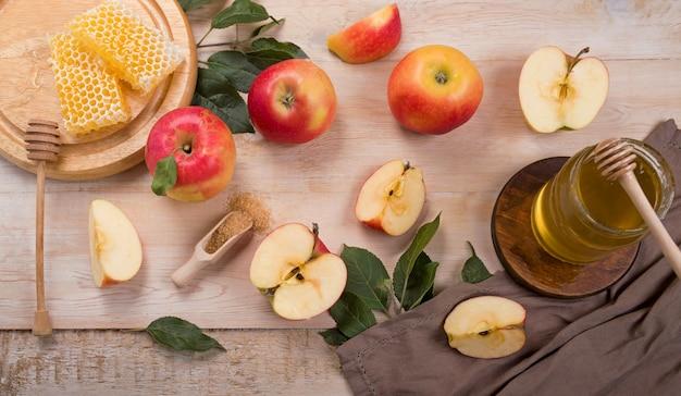 Superfície de rosh hashaná feriado judaico com maçãs e mel no quadro-negro. vista de cima. postura plana