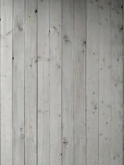 Superfície de tábuas de madeira brancas gastas na posição horizontal.