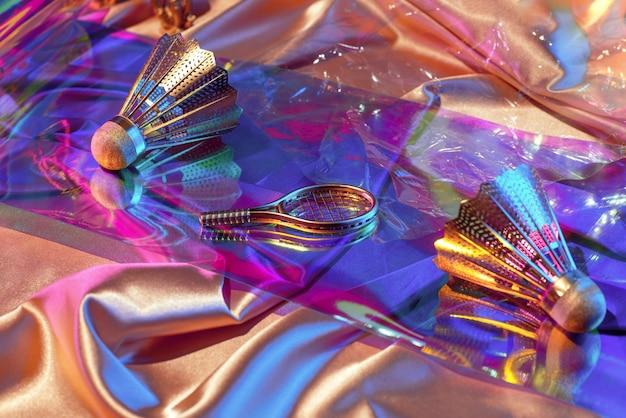 Superfície de tecidos iridescentes de arco-íris holográfico e objetos da peteca dos anos 90, raquete, fita cassete, retrospectiva dos anos 80, conceito esportivo.