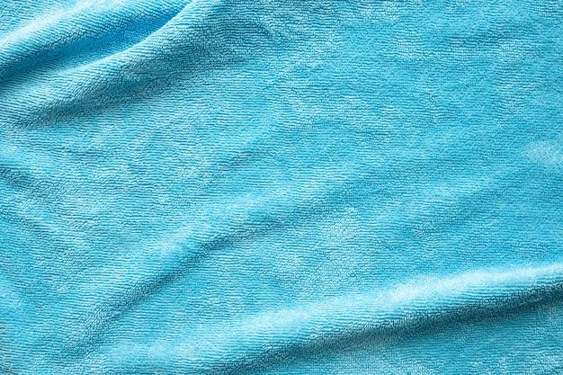 Superfície de textura de tecido de toalha azul perto do fundo
