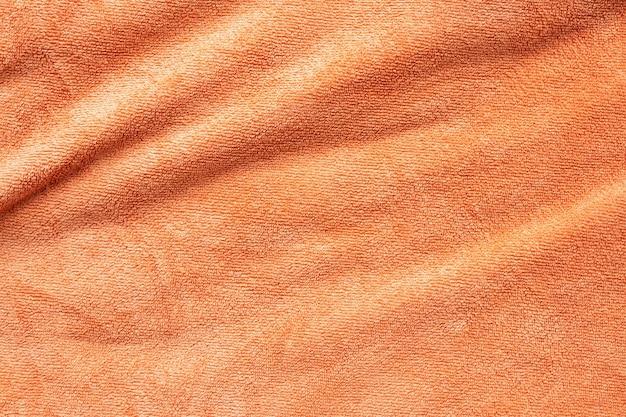 Superfície de textura de tecido de toalha laranja close-up do fundo