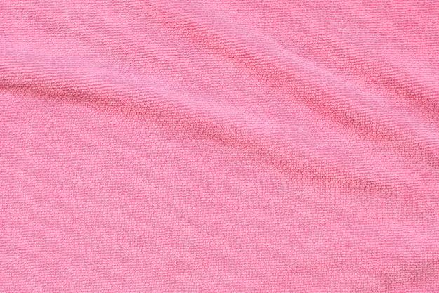 Superfície de textura de tecido de toalha rosa perto do fundo