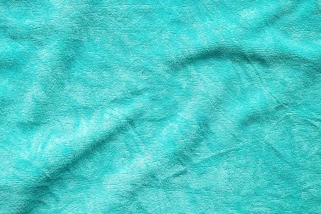 Superfície de textura de tecido de toalha verde perto do fundo