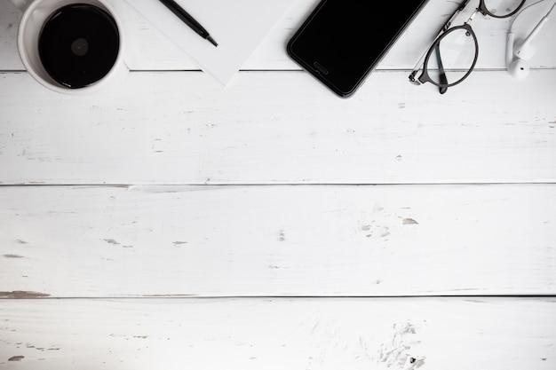 Superfície de uma mesa de madeira com notebook, smartphone, óculos e caneta, vista superior