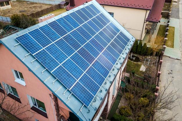 Superfície do close-up do iluminado pelo sistema voltaico solar azul dos painéis da foto solar do sol no telhado da construção. conceito de produção de energia verde ecológica renovável.