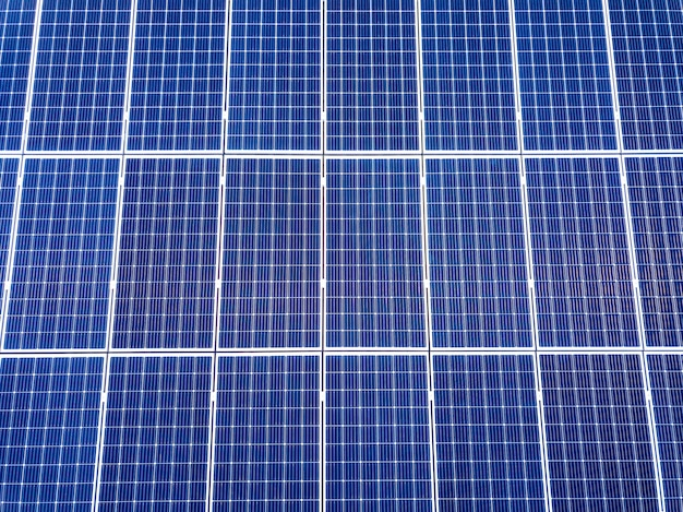Superfície do close-up do sistema voltaico azul brilhante dos painéis da foto solar no telhado da construção. conceito de produção de energia verde ecológica renovável.