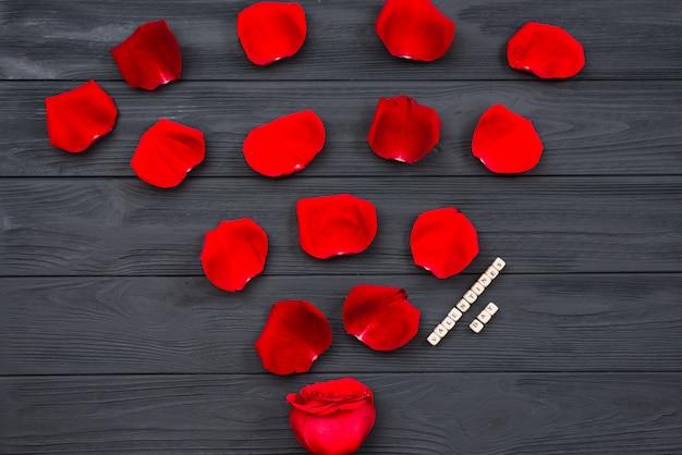 Superfície do piso texturizado de madeira escura, coberto com pétalas de rosa vermelhas