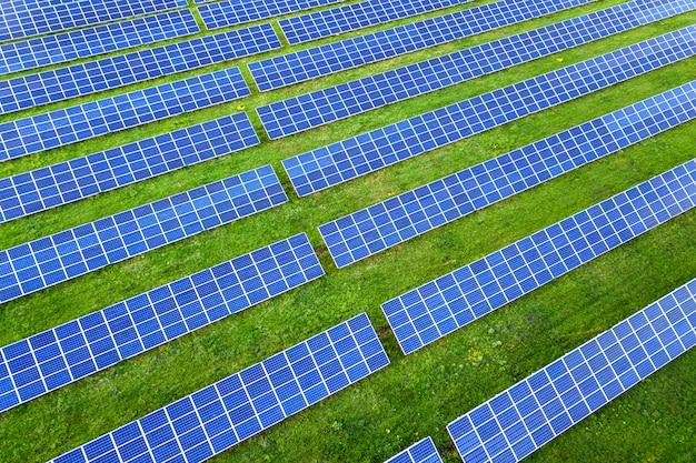 Superfície do sistema de painéis solares foto voltaica produzindo energia limpa renovável em fundo verde grama.