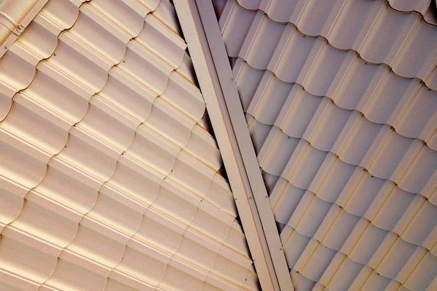 Superfície do telhado da casa coberta com telhas de metal marrom.