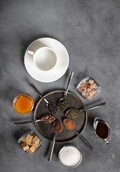 Superfície escura de café, chá, cacau, açúcar, mel e uma xícara de porcelana branca, vista superior,