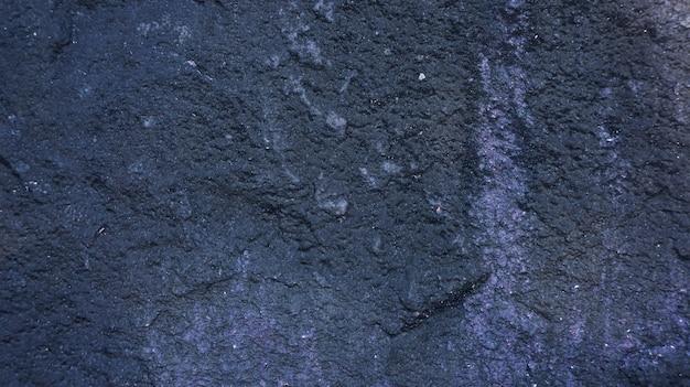 Superfície escura de uma pedra para um fundo.
