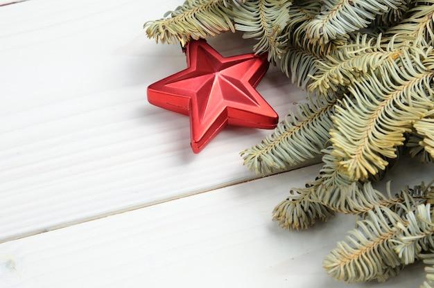 Superfície estampada de madeira branca de natal com galhos de árvores de natal e brinquedos