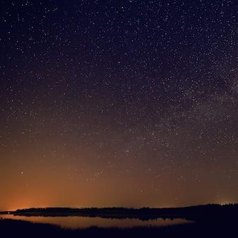Superfície lisa do lago em um fundo do céu estrelado