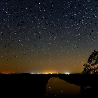 Superfície lisa do rio em um fundo do céu estrelado