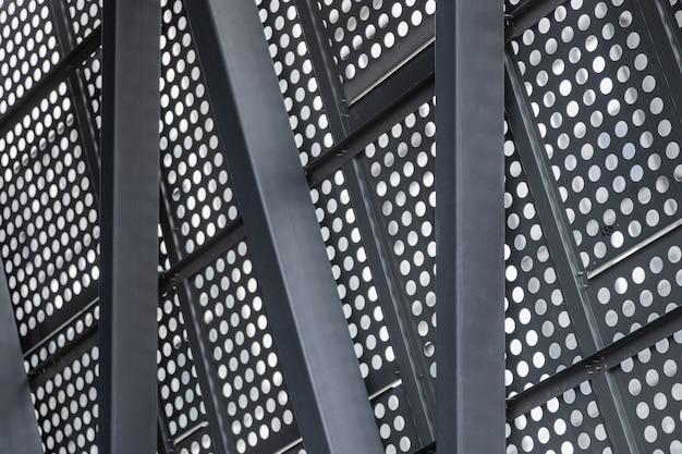 Superfície metálica com aberturas redondas apoiadas em vigas de ferro