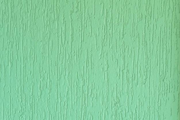 Superfície rebocada de uma parede verde ranhurada. no brasil conhecido como grafiato.