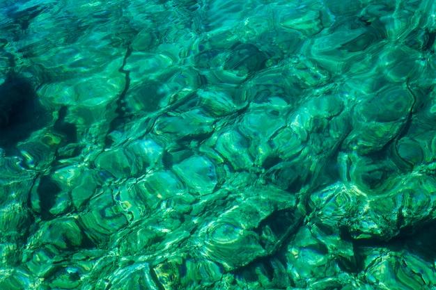 Superfície transparente mar turquesa clara com reflexo do sol.