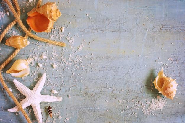 Superfície vintage azul com conchas, estrelas do mar e uma corda