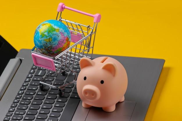 Supermercado global. cofrinho, carrinho de compras com um globo no teclado do laptop, close-up