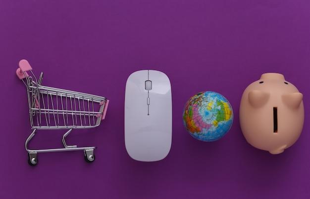 Supermercado global online. mouse de pc e mini carrinho de compras com globo, cofrinho em fundo roxo. vista do topo. postura plana