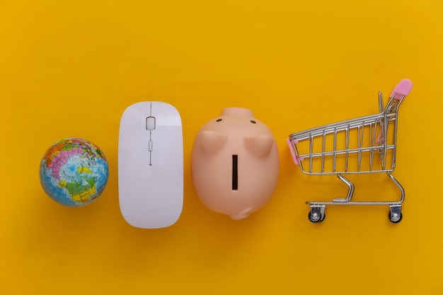Supermercado global online. mouse do pc e mini carrinho de compras com globo, cofrinho em fundo amarelo. vista do topo. postura plana