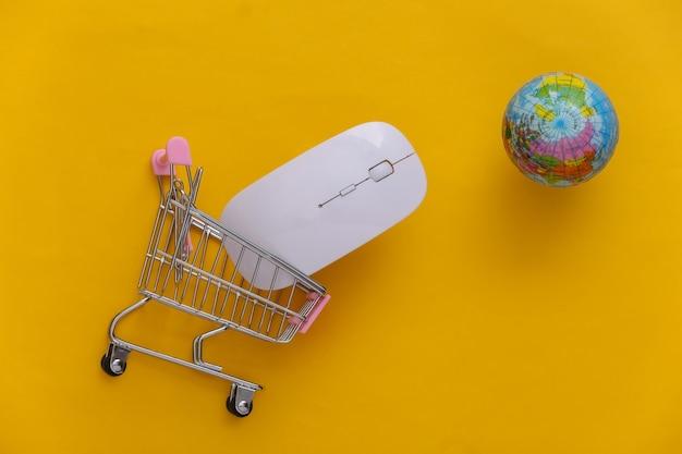 Supermercado global online. mouse do pc e mini carrinho de compras com globo sobre fundo amarelo. vista do topo. postura plana
