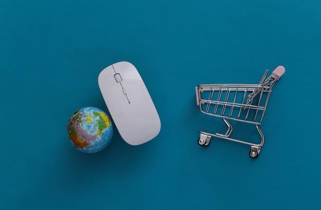 Supermercado global online. mouse do pc e mini carrinho de compras com globo sobre fundo azul. vista do topo. postura plana