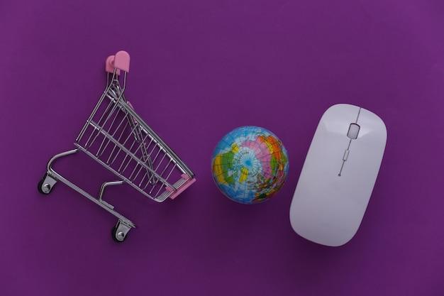 Supermercado global online. mouse do pc e mini carrinho de compras com globo sobre fundo roxo. vista do topo. postura plana