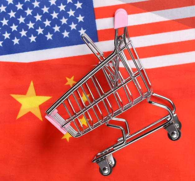 Supermercado internacional, global. mini carrinho de compras no fundo da bandeira turva dos eua e da china. conceito de compras.