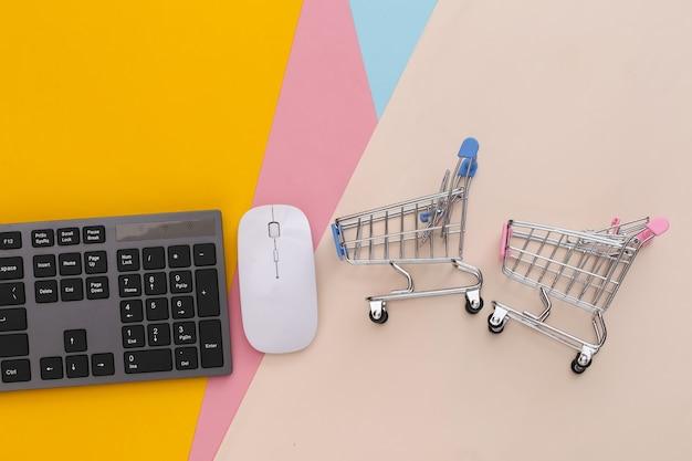 Supermercado online. teclado de pc e carrinho de compras em mesa colorida