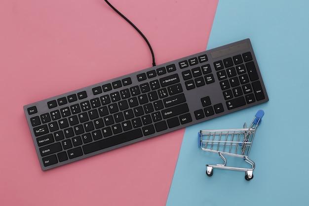 Supermercado online. teclado de pc e carrinho de compras em rosa azul pastel