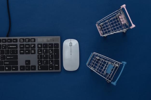 Supermercado online. teclado de pc e carrinho de compras em um azul clássico