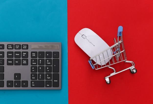 Supermercado online. teclado de pc e carrinho de compras em vermelho azul