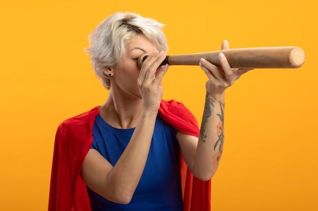 Supermulher confiante com capa vermelha segurando um taco de beisebol na frente do olho isolado na parede laranja