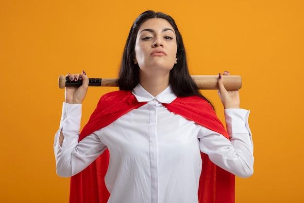 Supermulher jovem confiante segurando um taco de beisebol atrás do pescoço, olhando para frente, isolado na parede laranja