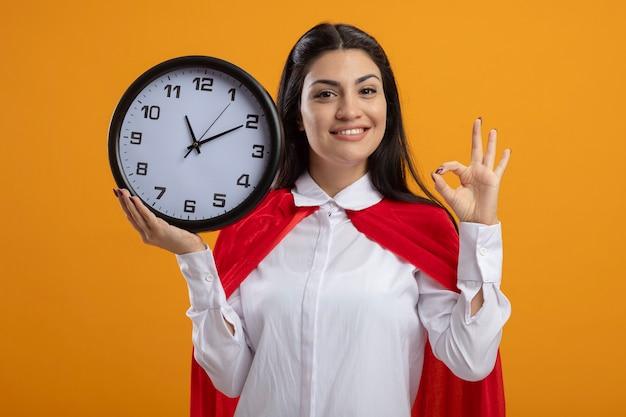 Supermulher jovem sorridente segurando o relógio olhando para a frente fazendo um sinal de ok isolado na parede laranja