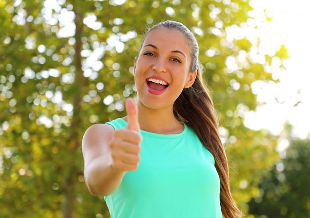 Supermulher! retrato da garota vencedora aparecendo o polegar. mulher saudável de sorriso positivo de aptidão ao ar livre.