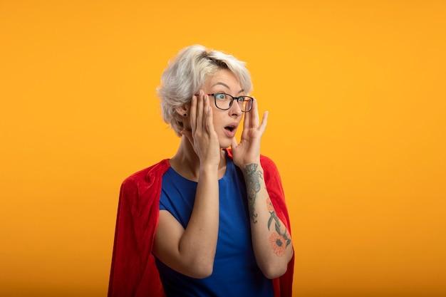 Supermulher surpresa com capa vermelha em óculos óticos olhando para o lado isolado na parede laranja