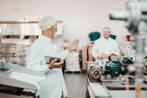Supervisor adulto sênior branco conversando com seu colega mais jovem sobre a qualidade dos alimentos. homem segurando o tablet. ambos estão vestidos com uniformes brancos e com rede no cabelo. interior da planta alimentar.