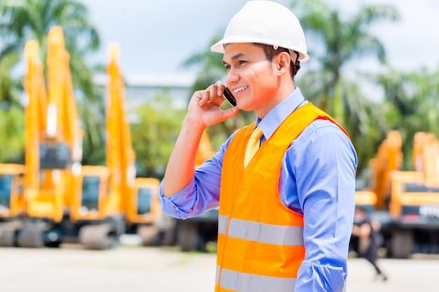 Supervisor asiático telefonando no canteiro de obras