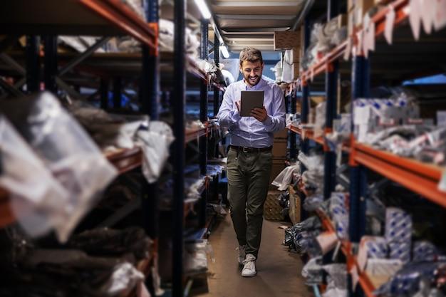 Supervisor barbudo andando pelo armazenamento da empresa de exportação, verificando as mercadorias e usando tablet.