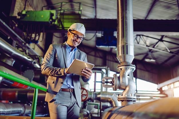 Supervisor caucasiano de sorriso considerável no terno e com o capacete na cabeça usando a tabuleta ao estar na usina.
