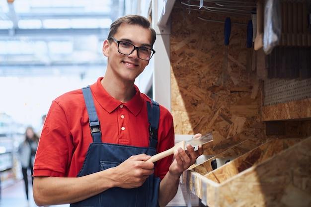 Supervisor com uma prancheta perto de caixas de pregos