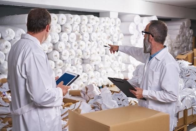 Supervisor de armazém e gerente homens com têxteis
