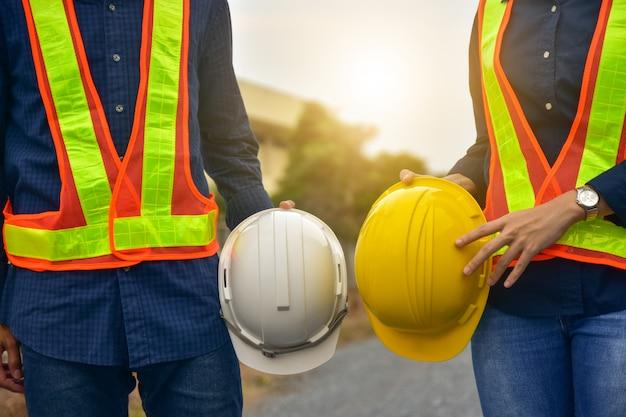 Supervisor de capataz duas pessoas segurando a construção de capacete