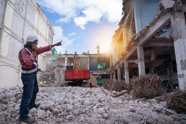 Supervisor de controle de demolição ou engenheiro, walkie-talkie na mão e apontar o dedo