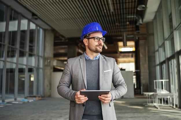 Supervisor de pé no edifício em processo de construção, segurando o tablet e verificando as obras