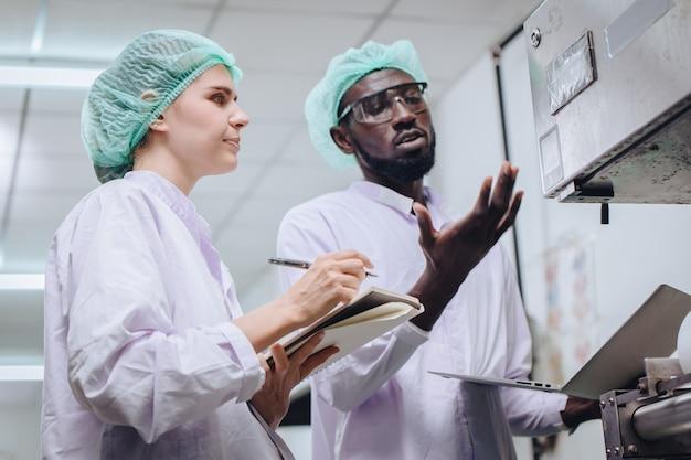 Supervisor de produção de mulher trabalhando com um trabalhador africano em uma fábrica de alimentos para verificar e relatar o problema da máquina ao engenheiro na linha de produção.