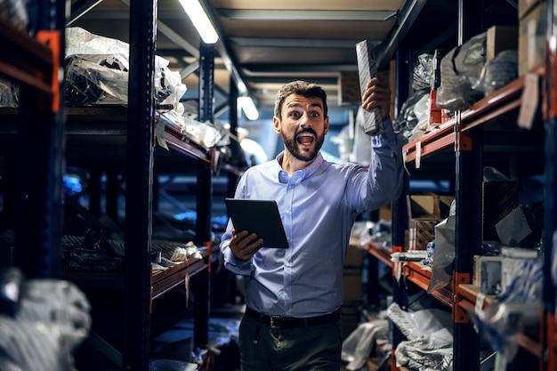 Supervisor em pé no armazém na fábrica, segurando o tablet e mostrando para a caixa do funcionário com ferramentas.