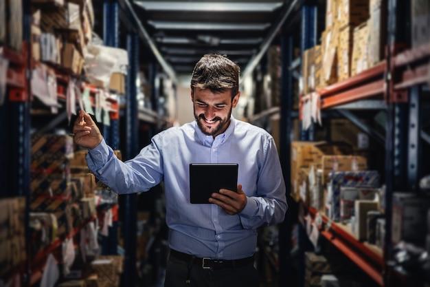 Supervisor em um depósito cheio de caixas e verificando as mercadorias prontas para entrega.